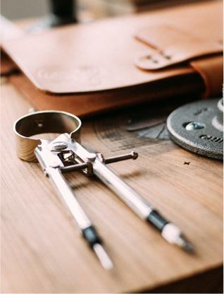 fotó fa asztalra helyezett körzőről, bőr táskáról